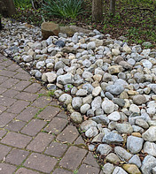 Path with pavers next to river rock